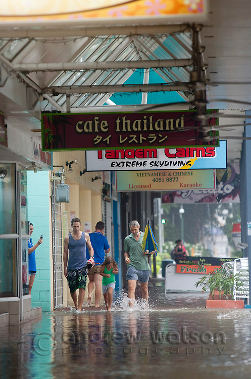 Locals pass shops flooded due to torrential rain and king tides on Aplin Street.  Cairns, Queensland, Australia