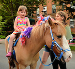 Garden City, New York, U.S. - June 6, 2014 -  A young girl rides a pony at the 17th Annual Garden City Belmont Stakes Festival, celebrating the 146th running of Belmont Stakes at nearby Elmont the next day. There was street festival family fun with live bands, food, and more, and a main sponsor of this Long Island night event was The New York Racing Association Inc.