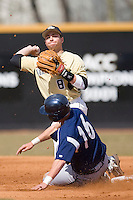 Second baseman Bentley Heyman #8 of the Wake Forest Demon Deacons turns a double play as Patrick Paligraf #16 of the Xavier Musketeers slides into second base at Wake Forest Baseball Park March 7, 2010, in Winston-Salem, North Carolina.  Photo by Brian Westerholt / Four Seam Images