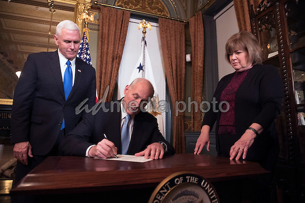 Retired Marine General James Kelly signs his confirmation paperwork after being sworn-in as Secretary of Homeland Security by Vice President Mike Pence (L), in the Vice Presidential ceremonial office in the Executive Office Building in Washington, D.C. on January 20, 2017. Photo Credit: Kevin Dietsch/CNP/AdMedia