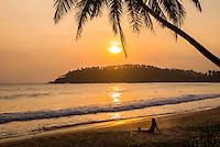 Mirissa, woman sitting on Mirissa Beach watching the sun set, South Coast of Sri Lanka, Southern Province, Asia. This is a photo of a woman sitting on Mirissa Beach watching the sun set, Sri Lanka, Asia.