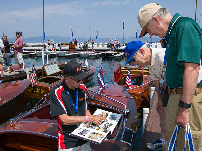 Stephen Hamill, left, shows off his wooden boat during the Concours d'Elegance Wood Boat Show at Lake Tahoe on Friday, August 10, 2018.