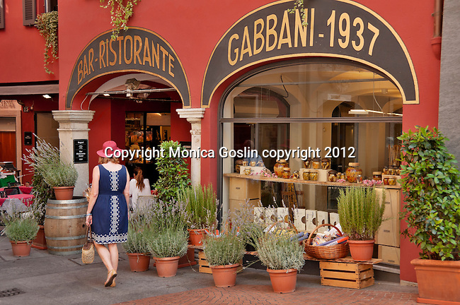 A woman wearing a blue dress and a red straw hat stands walks past the D. Gabbani restaurant and deli in Lugano, Switzerland.