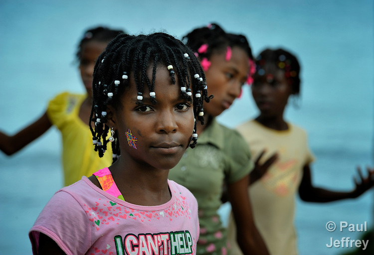 """Sandra Bourciquot and other members of Nouvel Etwal - Haitian Kreyol for """"New Stars"""" - dance on the beach at Jacmel, Haiti. Nouvel Etwal is a dance and creative movement group of 16 girls from age 8 to 13, based in the southern village of Mizak. According to Valerie Mossman-Celestin, an organizer of the group, """"Nouvel Etwal seeks to empowers girls to be self-confident and creative. The girls learn flexibility, discipline and teamwork, lessons they also need for life. Nouvel Etwal promotes health, well-being and enhanced self-worth. The girls are encouraged to live into a brighter future where girls and women are valued,  educated, and have equal opportunity to achieve their potential."""""""