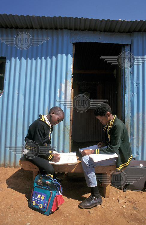 © Giacomo Pirozzi / Panos Pictures..Johannesburg, South Africa..Boys doing their homework outside their home in Soweto.