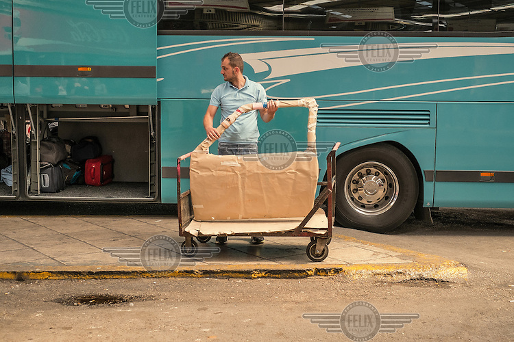 ATHENS, GREECE: Bus station. A man holds a car door before sending it somewhere in a passengers bus.