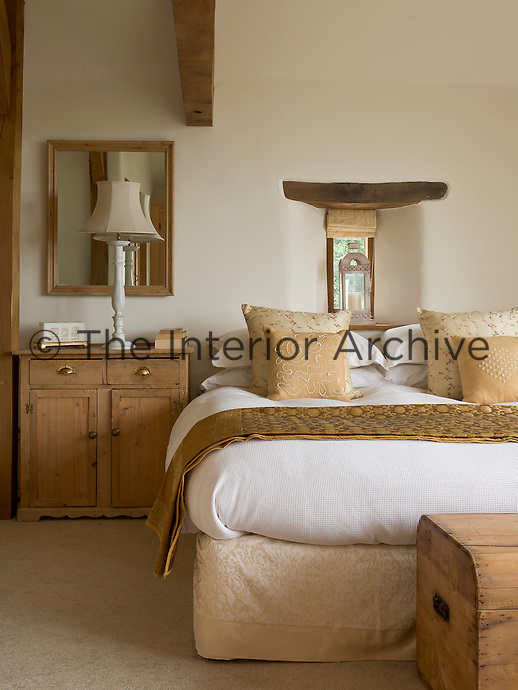 Embroidered cushions and a textile throw add texture to the bed in the master bedroom which is furnished with pine pieces