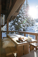 A minimal wooden table flanked by a pair of matching benches on a balcony overlooking the snow-covered slopes of the Alps