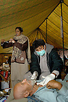 "Following an October 8, 2005, earthquake in northern Pakistan, members of Action by Churches Together in Pakistan, including Church World Service and the Church of Pakistan, responded quickly to the needs of thousands of affected families. Here a physician from Peshawar, Hizkial Barkat (with mask), a member of a CWS-supported delegation from the Peshawar diocese of the Church of Pakistan, attends to injured patients at a CWS-sponsored ""tent city"" near Balakot. Assisting him is Nassreen Shaker, a nurse from the Peshawar diocese."