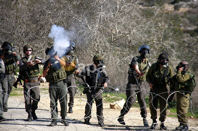 Israeli border police officers fire tear gas towards Palestinian demonstrators, not seen, during a protest in the village of Kufr Qaddum near the Israeli settlement of Kdumim, in the northern West Bank, Friday, Dec. 2, 2011. Photo by Wagdi Eshtayah