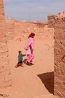 A couple walk on December 12, 2003, in the Saharawi refugee camps in Aljer. Saharawi people have been living at the refugee camps of the Algerian desert named Hamada, or desert of the deserts, for more than 30 years now. Saharawi people have suffered the consecuences of European colonialism and the war against occupation by Moroccan forces. Polisario and Moroccan Army are in conflict since 1975 when Hassan II, Moroccan King in 1975, sent more than 250.000 civilians and soldiers to colonize the Western Sahara when Spain left the country. Since 1991 they are in a peace process without any outcome so far. (Ander Gillenea / Bostok Photo)