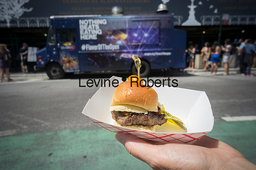 """A foodie displays her sample of a David Burke Filet Slider in Madison Square in New York on Monday, August 11, 2014 at the US Open food truck. The US Tennis Association (USTA) is promoting eating at the Open, which has a reputation for serving notoriously over-priced food, with a food truck visiting the city serving gourmet items from celebrity chefs and from the Open's """"Food Village"""" Samples include Lobster Roll and David Burke Filet Slider. The US Open runs from Aug. 25 through Sept. 8 in Arthur Ashe Stadium in Queens.  (© Richard B. Levine)"""