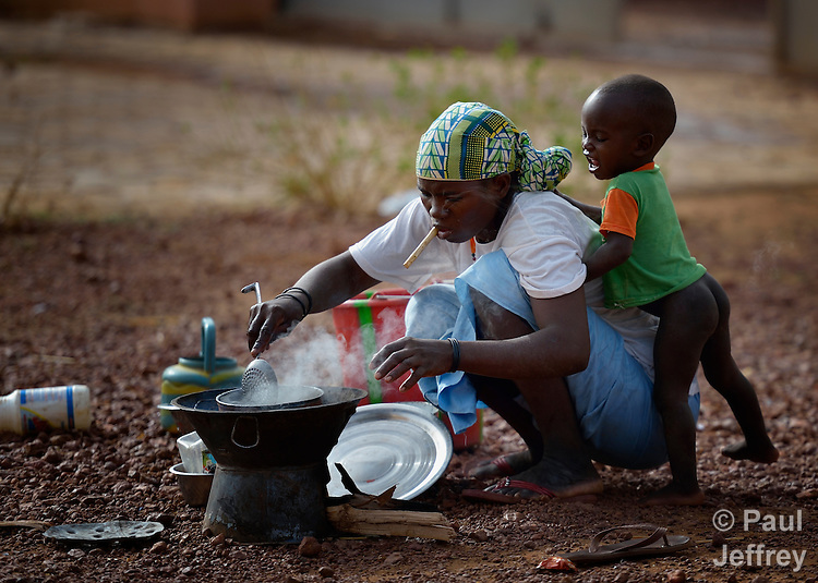 A boy pesters his mother as she cooks breakfast in a camp in Mopti, Mali, for families displaced by the fighting in the north of the country. Islamist rebels seized control of the north of Mali in 2012, but were chased out in early 2013 by French troops. Many displaced and refugee families have yet to return, preferring to wait for better security and improved economic conditions in the north.
