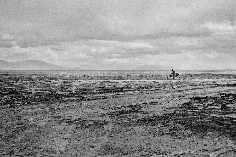 A Bolivian peasant rides a bicycle on a vast mountain plateau close to Oruro, Bolivia, 17 July 2002.