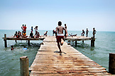 BELIZE, Hopkins, a boy runs down a dock towards the water, Caribbean Sea