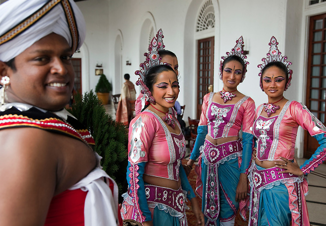 "Traditional dancers and musicians prepare to lead a fanfare at a morning wedding reception at The Galle Face Hotel. Founded in Colombo, Sri Lanka in 1864, is the oldest hotel east of Suez. It is located off Galle Road, the main highway in the City of Colombo.The hotel borrowed its name from this charming way back of ""Galle Face Green"" in 1864, built by four British entrepreneurs who were looking to start a business in the city..Mignonne Fernando and The Jetliners regularly entertained guests at the Coconut Grove, the night club attached to the hotel. The venue was even popularised in a song. Radio Ceylon recorded music programmes from the Coconut Grove as well as the Galle Face Hotel itself, presented by some of the legendary Radio Ceylon announcers in the 1950s and 1960s, such as Livy Wijemanne and Vernon Corea. Thousands listened to the broadcasts, particularly 'New Year's Eve' dances from the Galle Face Hotel..D.G. William (known as 'Galle Face William'), the Lanka Sama Samaja Party trade union leader, first worked and organised workers here. The Science fiction author Arthur C. Clarke wrote the final chapters of 3001 - The Final Odyssey in the hotel..It regularly featured on the itineraries of royalty . Princess Alexandra of Denmark commented that 'the peacefulness and generosity encountered at the Galle Face Hotel cannot be matched'. Former guests include the first man in space, Yuri Gagarin, former British Prime minister Edward Heath, the journalist Eric Ellis and Prince Sadruddhin Aga Khan, Rigger Bone Sconi, Lord Louis Mountbatten, 1st Earl Mountbatten of Burma and Marshal Josip Broz Tito."