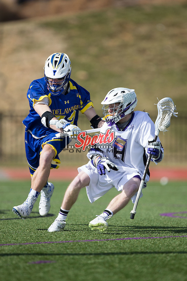 Matt Thistle (8) of the High Point Panthers is stick checked by Jackson Finigan (42) of the Delaware Blue Hens during first half action at Vert Track, Soccer & Lacrosse Stadium on February 1, 2015 in High Point, North Carolina.  The Panthers defeated the Blue Hens 15-10.   (Brian Westerholt/Sports On Film)