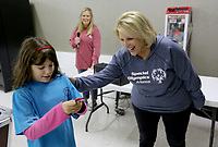 NWA Democrat-Gazette/DAVID GOTTSCHALK Anne Martinez-Schanber (left), a fifth grade student at Ruth Barker Middle School in Bentonville, receives a ribbon Wednesday, November 6, 2019, from Donna Kilmer, field representative Area 2 & 3 Special Olympics Arkansas at the Rogers Bowling Center in Rogers. Anne was competing in the two day Special Olympics of Arkansas Area Bowling Competition. Schools from eight districts participated in the competition.