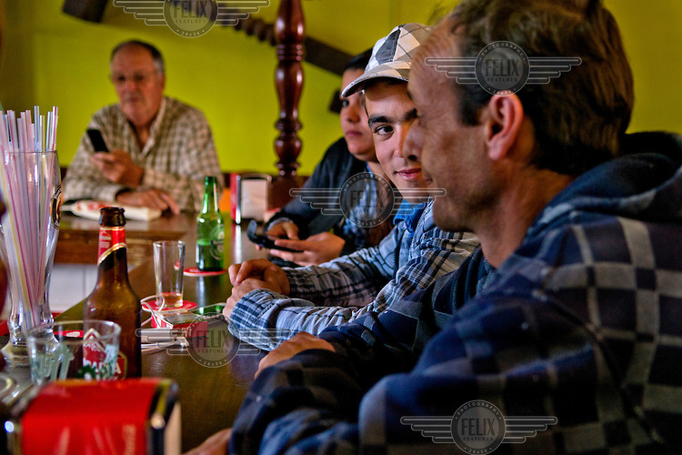 A group of men sit talking, drinking beer and checking their mobile phones at Bar Casa Pucho in Frontera, capital of Hierro. /Felix Features