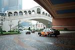 Macao - la ex colonia portoghese,dal 1997 ritornata alla Cina, è detta anche la las vegas d' oriente per i suoi numerosi Casino. ogni giorno migliaia di turisti attraversano lo stretto di mare che la divide dal continente per riversarsi nella sale da gioco. Oramai macao supera per fatturato Las Vegas. The venetian è uno dei casinò più grandi con all'interno una simil Venezia ricostruita. Si entra dopo essere passati sotto al Ponte di Rialto e si passeggia tra Piazza San Marco e il Bacino Orseolo. Qui una gondola a motore ma con finto gondoliere porta in giro i turisti. Mentre un falso cielo con le nuvole scorre sopra le nostre teste. NELLA FOTO L'ARRIVO ALL'HOTEL CASINO