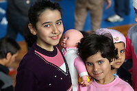 Pictured: Two young migrant girls with a toy doll smiling in Ierapetra basketball arena. Friday 28 November 2014<br /> Re: 700 migrants aboard a ship that lost power in the Mediterranean Sea with and was towed into a Greek harbor are being housed in a basketball arena while their refugee status was assessed.<br /> It took the Greek navy four days to tow the ship Baris from international waters into Ierapetra harbor, on the Greek island of Crete. The vessel lost power in storm-force winds.<br /> Many are Syrians fleeing the civil war. A senior health official on the island, Panayiotis Efstathiou, said many would be released.