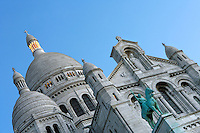 PARIS, FRANCE - JANUARY 20: An oblique low angle view of  Sacre-Coeur Basilica, on January 20, 2009, in Montmartre, Paris, France. Its clustered white domes are seen against a clear sky on a winter morning. In the foreground is the bronze equestrian statue of Joan of Arc by H Lefebvre which stands above the portico. Sacré-Coeur Basilica, built 1884-1914, was designed by Paul Abadie. Constructed in white travertine on the top of the Butte Montmartre, the Romano-Byzantine style Sacre-Coeur was designed as a monument to those who died in the Paris Commune during the Franco-Prussian War, 1870-71.  (Photo by Manuel Cohen)