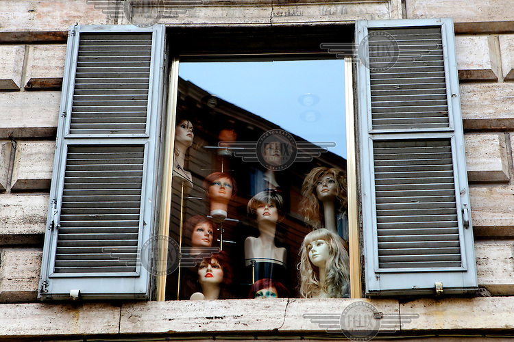 A window full of mannequin heads.