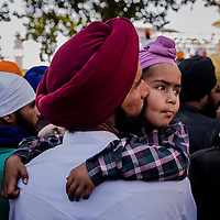 ANANDPUR SAHIB, INDIA - March 06, 2015: An Indian Sikh devotee Randhir Singh, 39, a labourer who works for Ranbaxy, kisses his son on Gurpreet Singh, 5 years old, from Fatehpur in Punjab, on the cheek,  as as they wait to enter the temple during a religious procession to mark Hola Mohalla at the Guru Dwara Sri Kesgarh Sahib temple at Sri Anandpur Sahib, during Hola Mohalla celebrations on March 06, 2015 in Anandpur Sahib, India. Hola Mahalla or simply Hola is a Sikh event, which takes place on the first of the lunar month of Chet, which usually falls in March, and sometimes coincides with the Sikh New Year. It was started by Guru Gobind Singh the tenth Sikh guru in 1701 AD. Hola Mohalla is a three day Sikh festival, in which Nihang Sikh 'warriors' perform Gatka (mock encounters with real weapons), tent pegging and bareback horse-riding. <br /> Daniel Berehulak for The New York Times