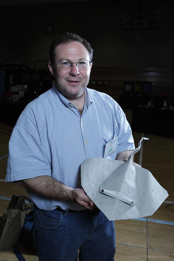 New York, NY, USA - June 24, 2011: Peter Engel, an Origami designer and folder with his original creation, a stingray at the OrigamiUSA Convention in New York.  Peter Engel is an American origami artist and theorist, science writer, graphic designer, and architect. He has written several books on Origami, including Origami from Angelfish to Zen, 10-Fold Origami: Fabulous Paperfolds You Can Make in Just 10 Steps!, and Origami Odyssey.