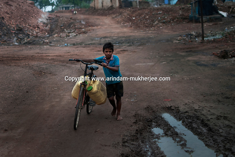 A young boy goes to fetch water at Bokapahari slum area in Jharia. This area is affected by mine fire causing damage to the water pipes .A huge coal mine fire is engulfing the city of Jharia from all its sides. All scientific efforts have gone in vain to stop this raging fire. This fire is affecting lives of people living in and around Jharia. Jharkhand, India. Arindam Mukherjee