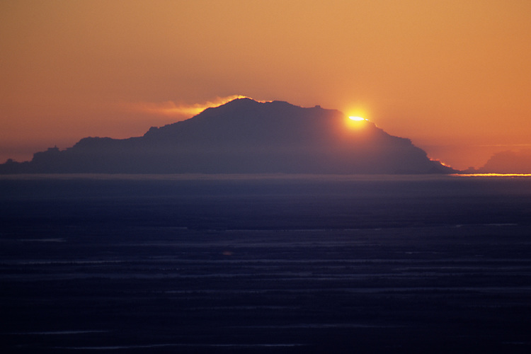 The setting sun passes behind Mount McKinley, illuminating snow blowing from its face, as seen from about 160 miles away near Fairbanks, Alaska, on a frigid cold December day. Temperature variations spanning the distance distort the mountain's face.