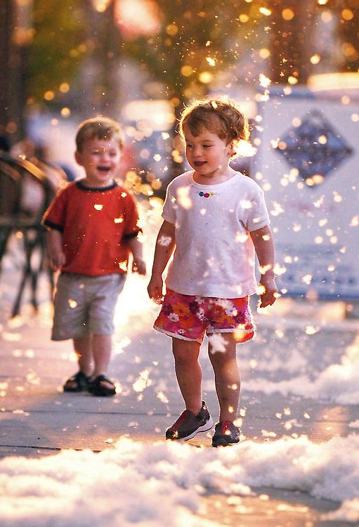 Two-year-old twins Michael, left, and Gracie McAuley-MacDonald of Easthampton frolic among cottonwood seeds while walking along Cottage Street in Easthampton, Massachusetts.