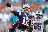 2 December 2012:  New England quarterback Tom Brady (12) passes as Miami linebacker Koa Misi (55) can only react with facial expressions in the third quarter as the New England Patriots defeated the Miami Dolphins, 23-16, at Sun Life Stadium in Miami Gardens, Florida.