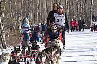 Jason Mackey and team run past spectators on the bike/ski trail during the Anchorage ceremonial start during the 2014 Iditarod race.<br /> Photo by Britt Coon/IditarodPhotos.com