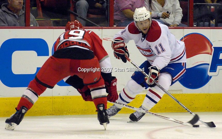 Montreal Canadiens' Saku Koivu (11) is defended by the Carolina Hurricanes' Trevor Letowski during their game Friday, Oct. 26, 2007 in Raleigh, NC. The Canadiens won 7-4.