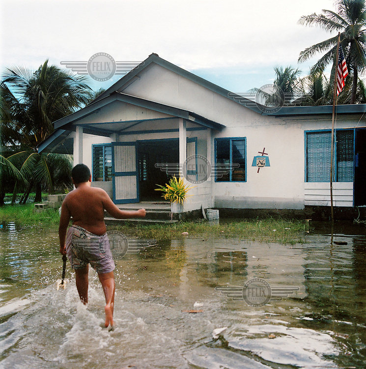 A young boy plays with his toy boat in floodwaters outside the Assembly of God church community building.  The coral atoll is to vulnerable to sea level rise, particularly at high spring tides, when salty water seeps up through the ground and causes flooding.