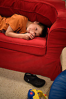"Jack Ursitii, age 7, plays on a couch during a ""sensory break"" in his home in Dover, Mass., on Monday, July 25, 2011. His teacher, Sarah Hoey from the Nashoba Learning Group, ""squishes"" Jack with a couch cushion, which is a favorite activity of Jack's. Jack has been diagnosed with autism.  After school at his home, Jack works with his teacher and a therapist to do educational and independent leisure activities. Periodically Jack takes ""sensory breaks"" to stop activity and play independently, allowing him to return to his tasks with greater concentration. During the ""sensory breaks"" Jack does a variety of things, including looking at his reflection, making faces, jumping on a small trampoline or cushions, or play with an iPad...Jack Ursitti wears a small GPS ankle bracelet at all times in case he runs off from his family or caretakers. The device will be activated if he goes missing, allowing police and other searchers to find him."