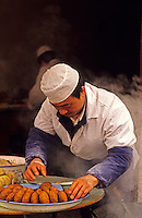 China. Xi'an. Xian.  Cook making rissoles in pavement/sidewalk restaurant..
