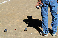 Man holding two boules while contemplating his next move, Provence, France.