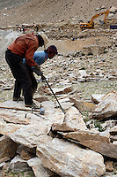 China started building a controversial 67-mile &quot;paved highway fenced with undulating guardrails&quot; to Mount Qomolangma, known in the west as Mount Everest, to help facilitate next year's Olympic Games torch relay./// Tibetan men break rocks with sledge hammers to build the road to Everest Base Camp. <br /> Tibet, China<br /> July, 2007