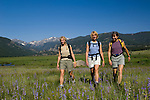 Girlfriends hiking in meadow of wildflowers on a clear, blue-sky summer morning at Moraine Park in Rocky Mountain National Park, Colorado