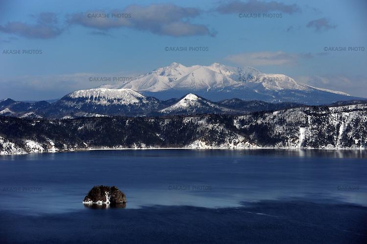 Lake Mashu in winter with snow covered mountains behind.<br /> <br /> Lac Mashu en hiver avec des montagnes couvertes de neige derrière.