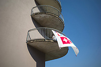 "Switzerland. Canton Ticino. Ponte Tresa. The inhabitants on the building's first floor have written a message on a white sheet hanged outside on their balcony which faces  Italy. The words say "" Together we will make it. Switzerland and Italy"". The flag of Switzerland displays a white cross in the centre of a square red field. The white cross is known as the Swiss cross. A woman is hanging wet clean clothes on the dryer. Due to the spread of the coronavirus (also called Covid-19)., the Federal Council has categorised the situation in the country as ""extraordinary"". It has issued a recommendation to all citizens to stay at home, especially the sick and the elderly. From March 16 the government ramped up its response to the widening pandemic, ordering the closure of borders, bars, restaurants, sports facilities and cultural spaces. Only businesses providing essential goods to the population – such as grocery stores, bakeries and pharmacies – are to remain open. Ponte Tresa is a municipality in the district of Lugano. 7.04.2020 © 2020 Didier Ruef"