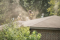 NWA Democrat-Gazette/ANTHONY REYES &bull; @NWATONYR<br /> A pair of Springdale fire fighters vent the roof Thursday, Sept. 3, 2015 to a structure fire at 1101 Backus Avenue in Springdale. The home was occupied at the time of the fire, but the resident was able to escape the fire on their own. The resident was transported with minor injuries to Northwest Medical Center Springdale. The cause of the fire is under investigation.