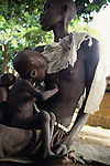 A child tries to breast  feed in Thiet feeding camp in Southern Sudan. Hundreds of Dinka tribes people having had their villages bombed and burnt  by the Khartoum forces  have travelled hundreds of miles to  avoid  starvation a the feeding centre.