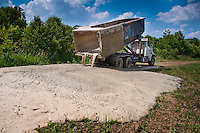 Lime sludge from a water treatment plant is unloaded along the edge of a farm field where it was laid for use in treating the field's ability to grow a variety of crops from corn and soybeans to wheat..