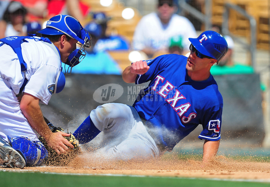 Mar. 16, 2012; Phoenix, AZ, USA; Texas Rangers base runner David Murphy (right) is tagged out at home by Los Angeles Dodgers catcher Mark Ellis in the first inning at The Ballpark at Camelback Ranch. Mandatory Credit: Mark J. Rebilas-