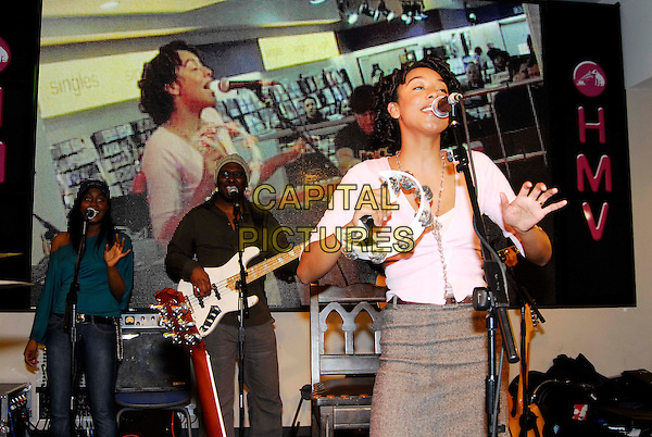 CORINNE BAILEY RAE.Instore Gig & Signing, HMV 150 Oxford Street,.London, England,.20th February 2006..half length pink top grey skirt concert music singer singing performing performance live guitar tambourine band.Ref: HT.www.capitalpictures.com.sales@capitalpictures.com.©Capital Pictures