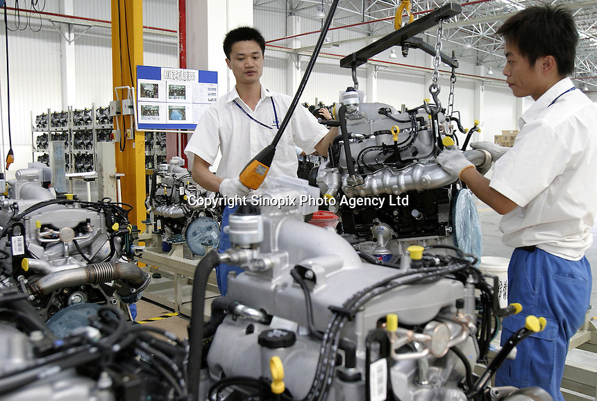 Two Chinese General Motors employees lift an engine about to be shipped to Canada at the Shanghai General Motors plant in Shanghai, China. The engines will be assembled on the GM model Equinox, which is a vehicle made of parts from around the world, very few of which are actually made in the USA..