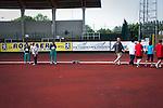 Epreuve de saut en hauteur au Spécial Olympic Belge. A droite les participants aux autres épreuves d'athléthisme sont accompagnés jusqu'au podium par les bénévoles. Les groupes si tiennent la main, afin que personne ne s'égare.